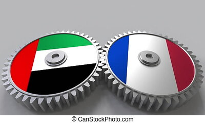 Flags of the UAE and France on meshing gears. International...