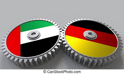 Flags of the UAE and Germany on meshing gears. International cooperation conceptual 3D rendering