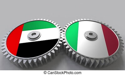 Flags of the UAE and Italy on meshing gears. International...