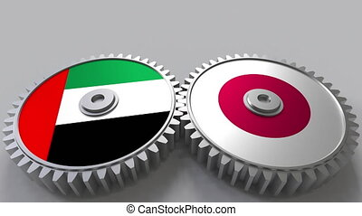 Flags of the UAE and Japan on meshing gears. International...