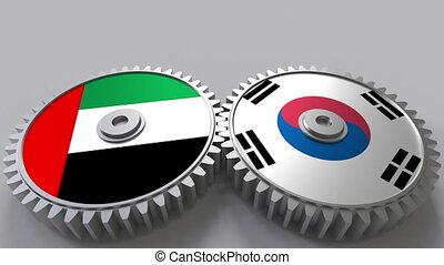 Flags of the UAE and Korea on meshing gears. International...