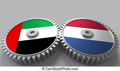 Flags of the UAE and Netherlands on meshing gears....