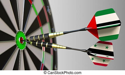 Flags of the UAE and Syria on darts hitting bullseye of the...