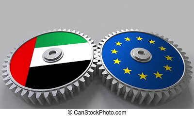 Flags of the UAE and the European Union on meshing gears....