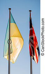 Flags of the Ukraine and United Kingdom on a blue clear sky...