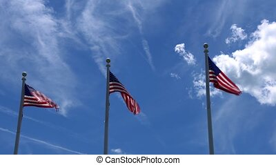 Flags of the United States waving over blue sky - Flags of...