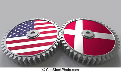 Flags of the USA and Denmark on meshing gears. International...