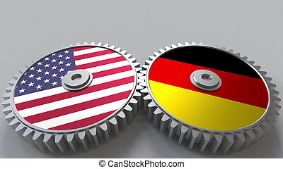 Flags of the USA and Germany on meshing gears. International cooperation conceptual 3D rendering