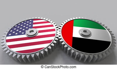 Flags of the USA and the UAE on meshing gears. International...