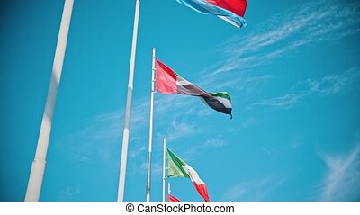 Flags of the world countries blowing in the wind on a background of the bright blue sky