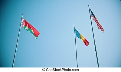 Flags of the world countries blowing in the wind on a background of the clear blue sky