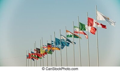 Flags of the world countries blowing in the wind on the background of clear beautiful sky