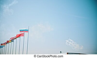Flags of the world countries blowing in the wind - several airplanes performing a show on the background