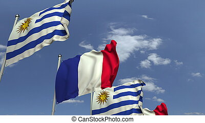 Flags of Uruguay and France against blue sky, 3D rendering