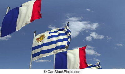 Flags of Uruguay and France against blue sky, loopable 3D...