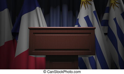 Flags of Uruguay and France and tribune, 3D rendering