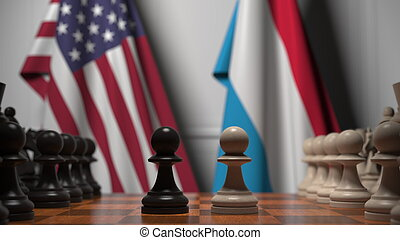 Flags of USA and Luxembourg behind pawns on the chessboard. ...