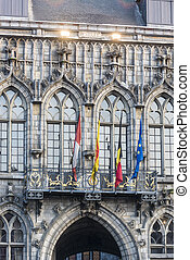Flags on City Hall facade in Mons, Belgium.
