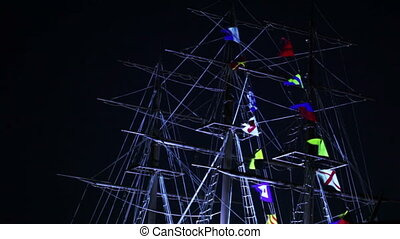 Flags on mast at night - Lighted flags on mast of sailing...