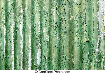 Flaky green paint on weathered corrugated iron.
