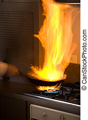 Flame fried - Chef in kitchen cooking in pan with big fire