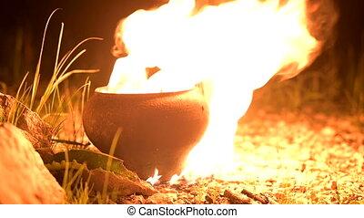 Flame in pot in dark. Fire Illuminates all around. Summer, ...