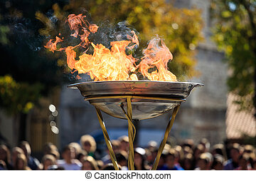 Flame lighting ceremony. Flame in front of blurred crowd -...