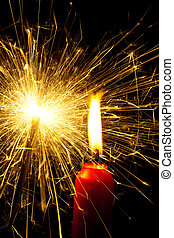 the flame of a candle brings light into the darkness. with sparkler for christmas