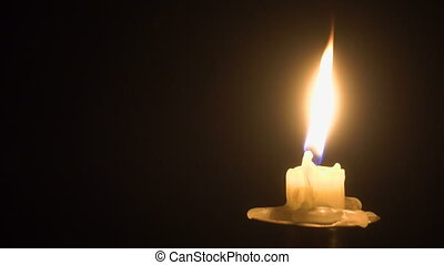 Flame of burning candle on the old brass candlestick over...