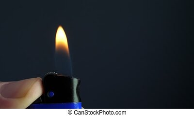 Flame of cigarette lighter in the dark. Close up and slow motion.