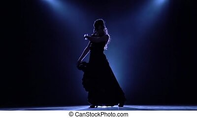 Flamenco. Dancer in the dark room performs elegant movements with her hands . Llight from behind. Smoke background. Silhouette. Slow motion