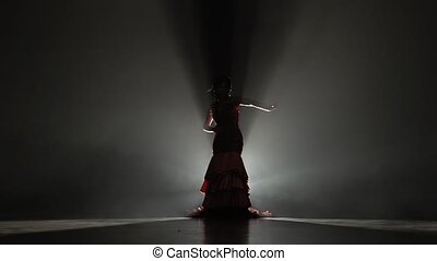 Flamenco. Girl dances flowing movements with her hands. Light from behind. Smoke background. Slow motion. Silhouette