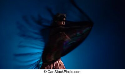 Flamenco. Girl is dancing with a manton in her hands . Light from behind. Smoke blue background. Slow motion