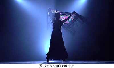 Flamenco. Girl is dancing with a manton in the hands of a Spanish incendiary dance. Llight from behind. Smoke background. Silhouette. Slow motion