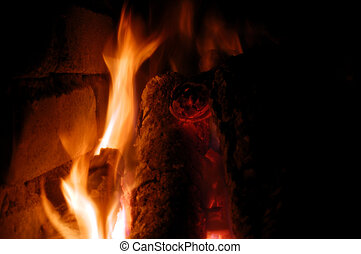 Flames of fire from the wood in a brick fireplace
