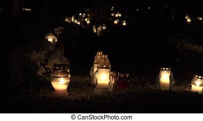 Flaming candles on the grave on All saints day at night....
