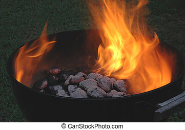 flaming charcoals - charcoals flaming hot in a kettle grill