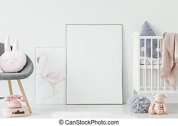 Flamingo poster standing on the floor behind empty mockup poster in white baby room interior with cute pillows and wooden crib. Place your photo here