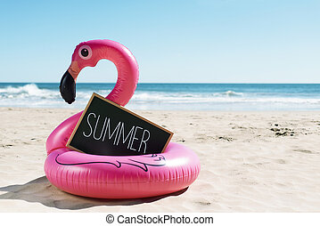 flamingo swim ring on the beach and text summer
