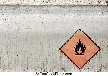 Flammable material weathered warning sign on rusty metal surface.
