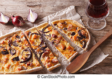 flammkuchen sliced pie and red wine close-up. horizontal - ...