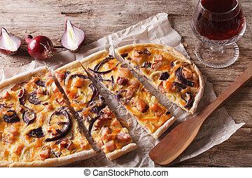 flammkuchen sliced pie and red wine close-up. horizontal -...