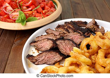 Flank steak with fries onion rings and salad...