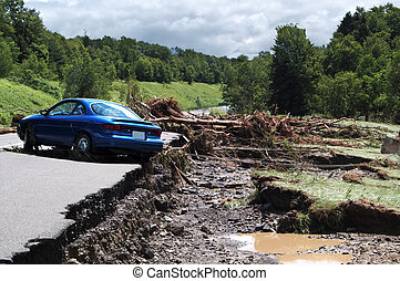 A car comes to rest next to washed out road way after being caught in a flash flood.