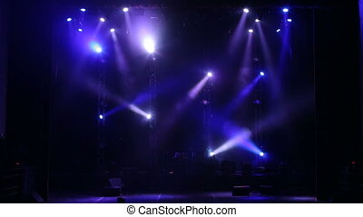 Flashing blue spotlights that illuminate the stage at a concert with fog.