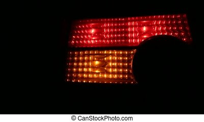 Flashing Car Light on Urban Road at Night