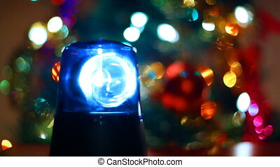 flashing lamp rotates in front of festive lights Christmas tree