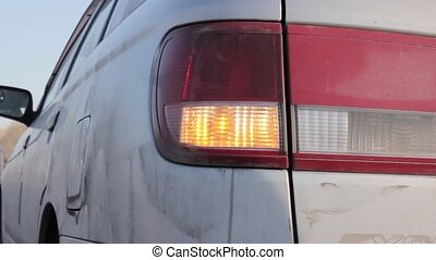 Flashing orange blinker light on rear lamp. car on a sidelines