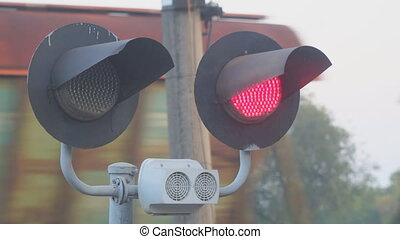 Flashing red light at the railway crossing on the background...