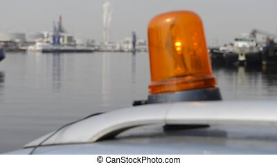 An orange flashlight on top of a car in an industrial harbor